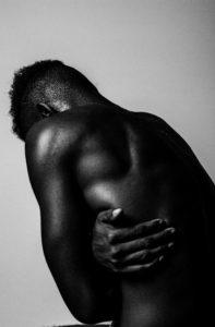 Homme de dos bras croisés enroulé sur sa douleur